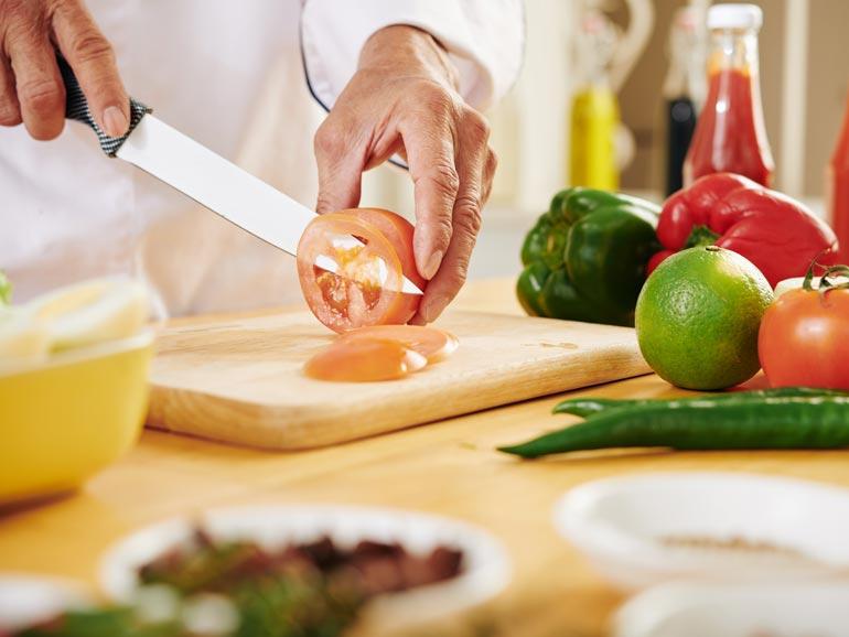 Hombre cortando un tomate sobre una tabla de cocina