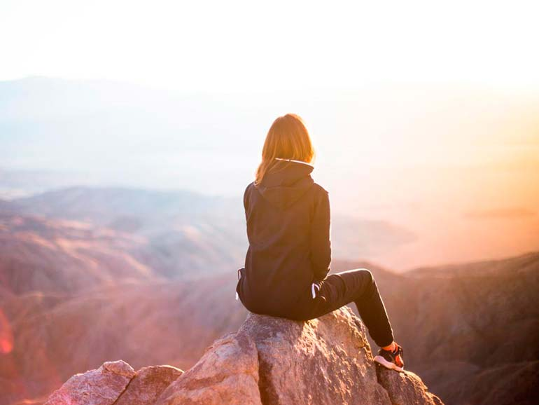 Mujer mirando al horizonte desde la cima de una montaña